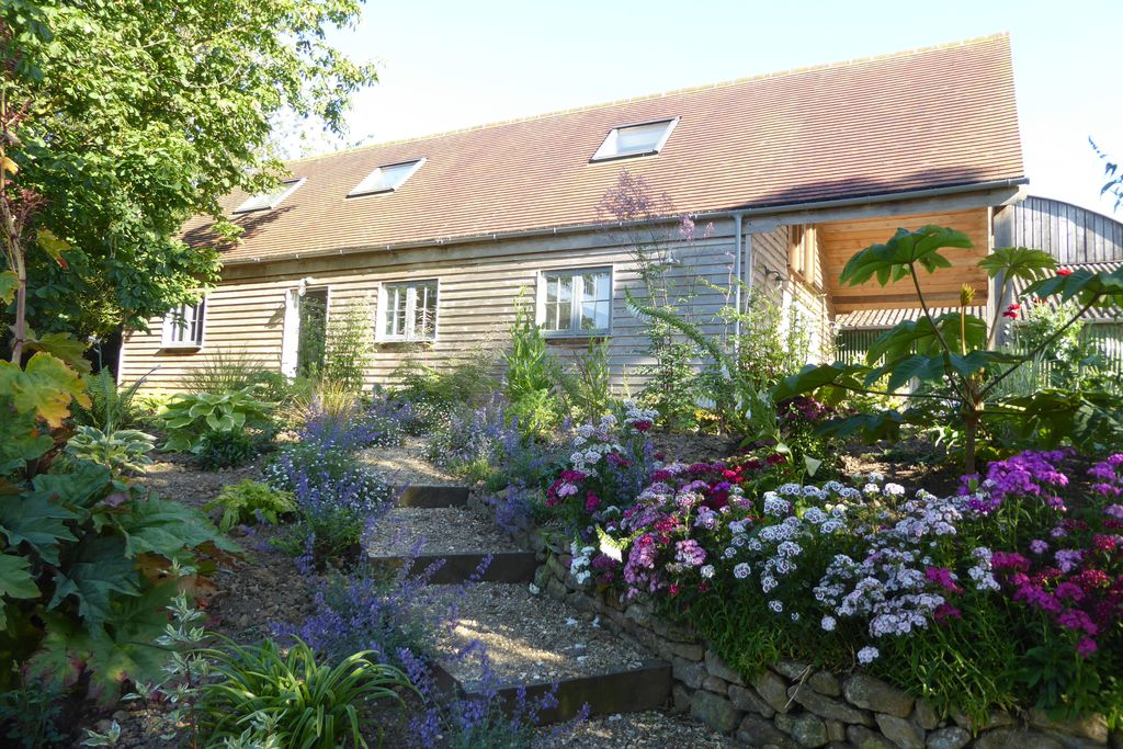 The Garden House at Holway Mill nestled in beautiful flowers in Dorset, England