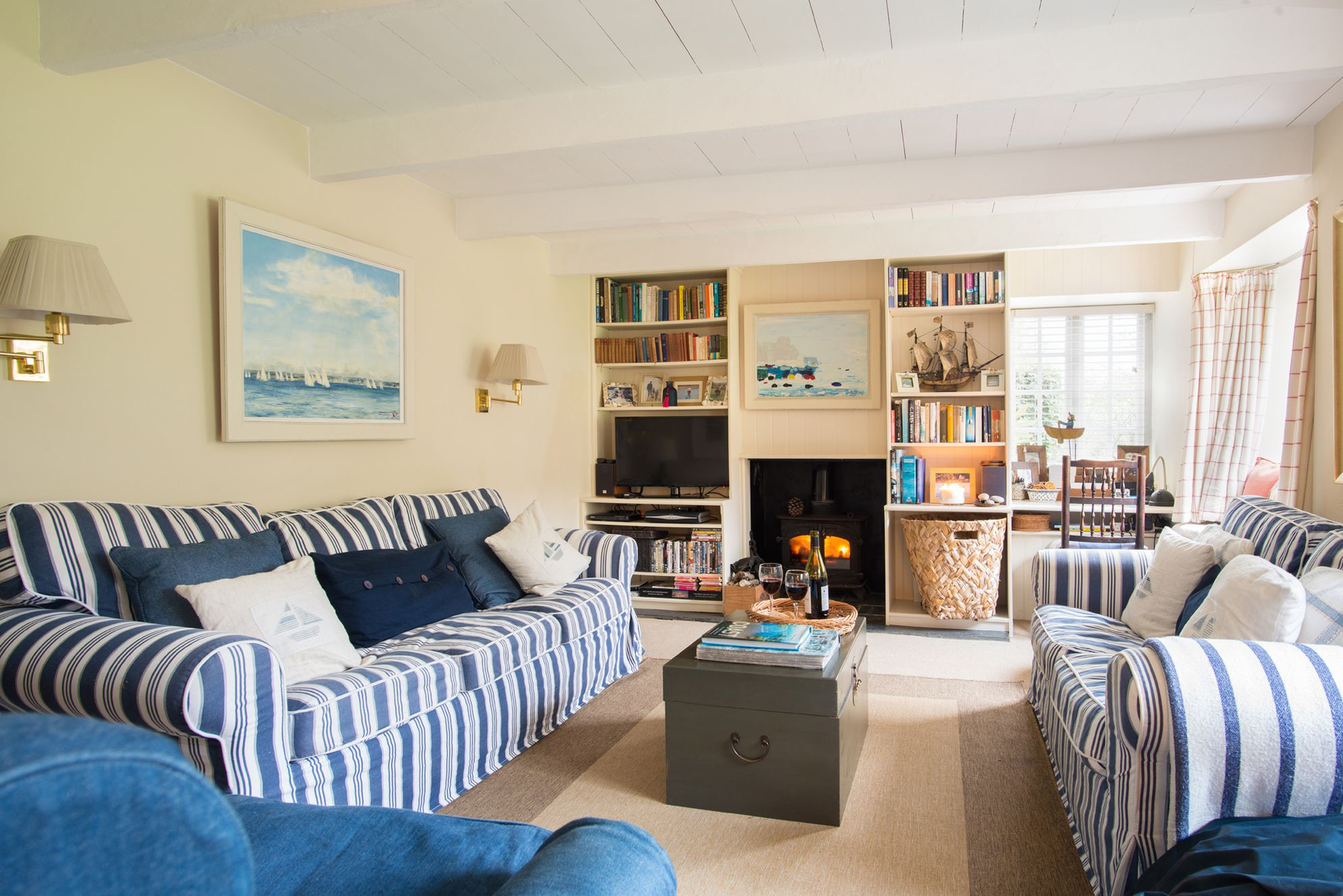 A warm Cornish living room with red wine and a woodburner
