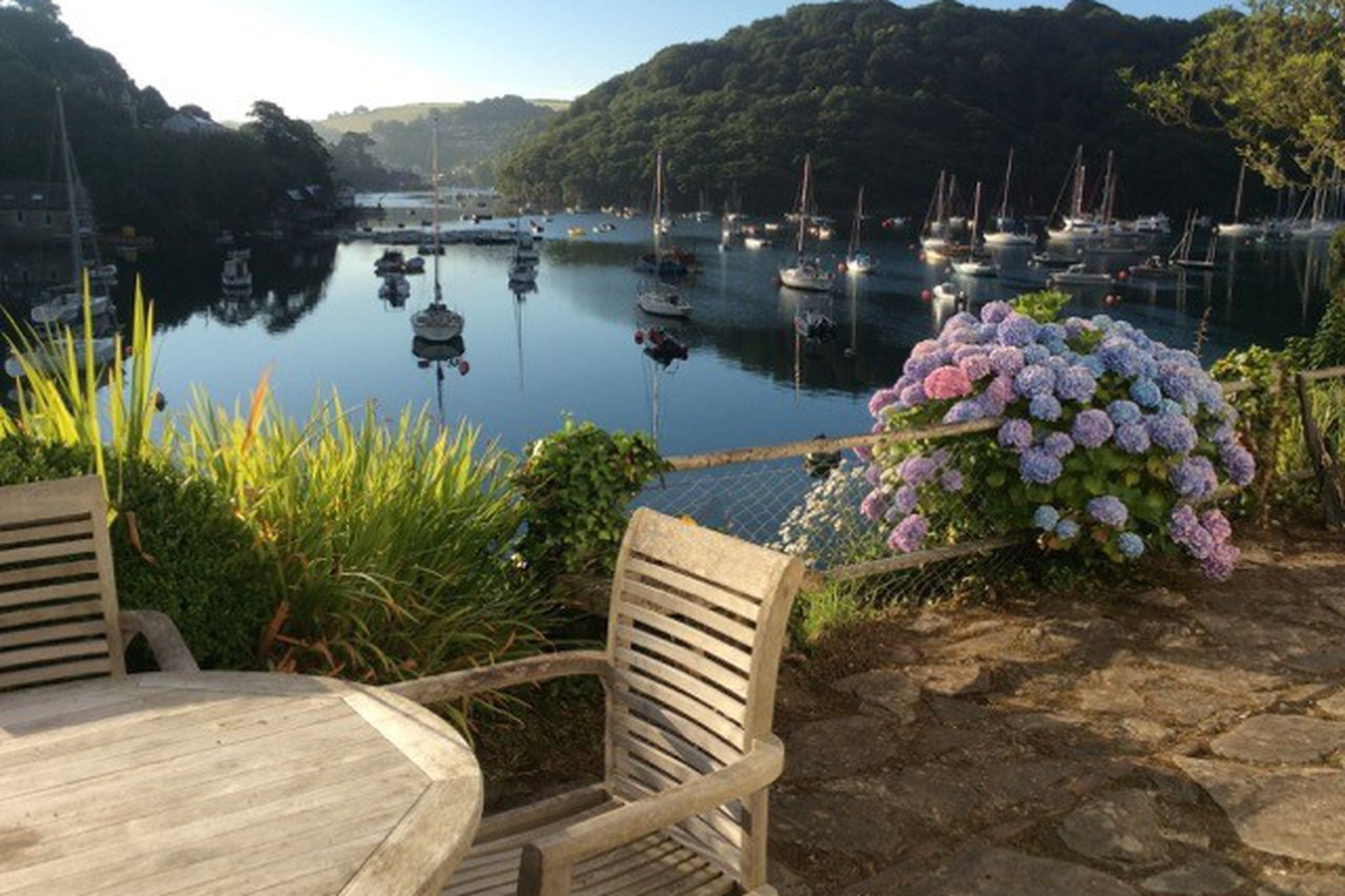 Patio with seating area overlooking the water at the Old Coastguards Cottage in Devon