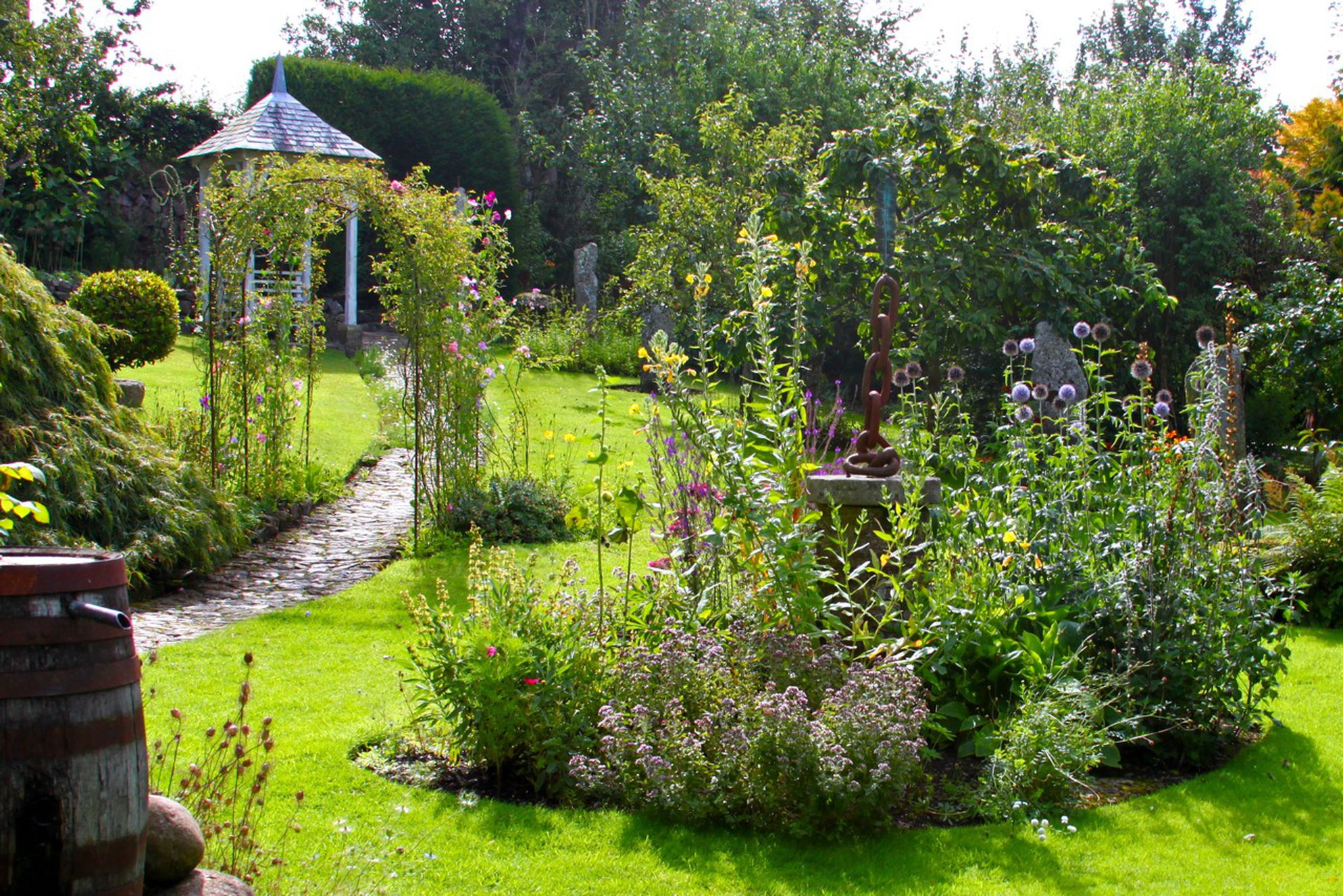 View of the lovely garden with the sculpture and pathway leading up the garden