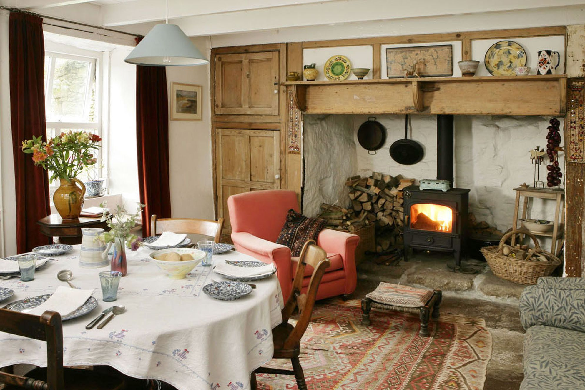 Living rrom with made up table and cosy seat in front of wood-burner
