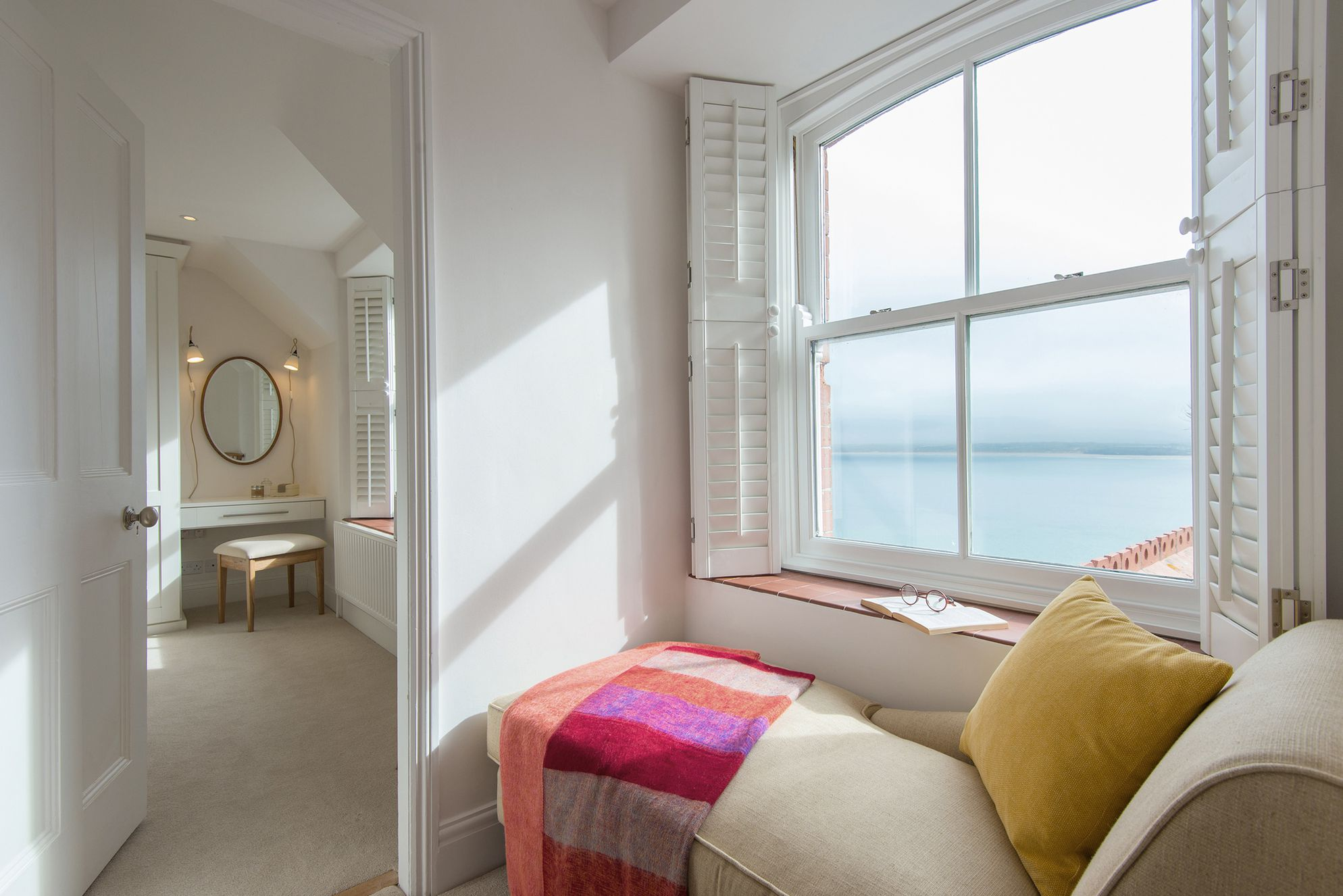 Window seat over looking the sea with a door leading to a dressing room