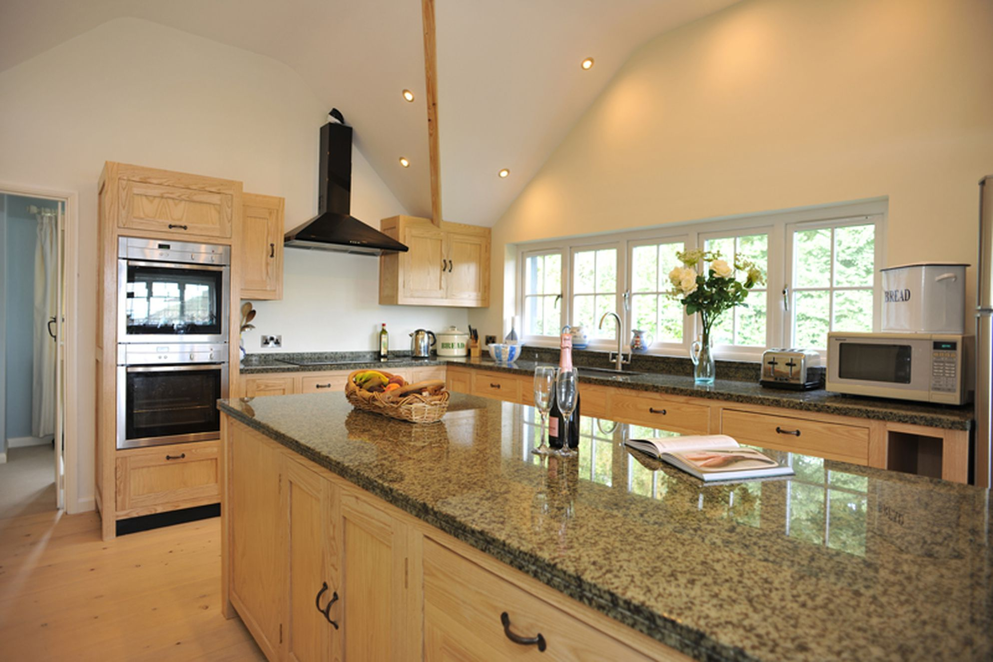 Large modern kitchen with a kitchen island and flowers on the worktop