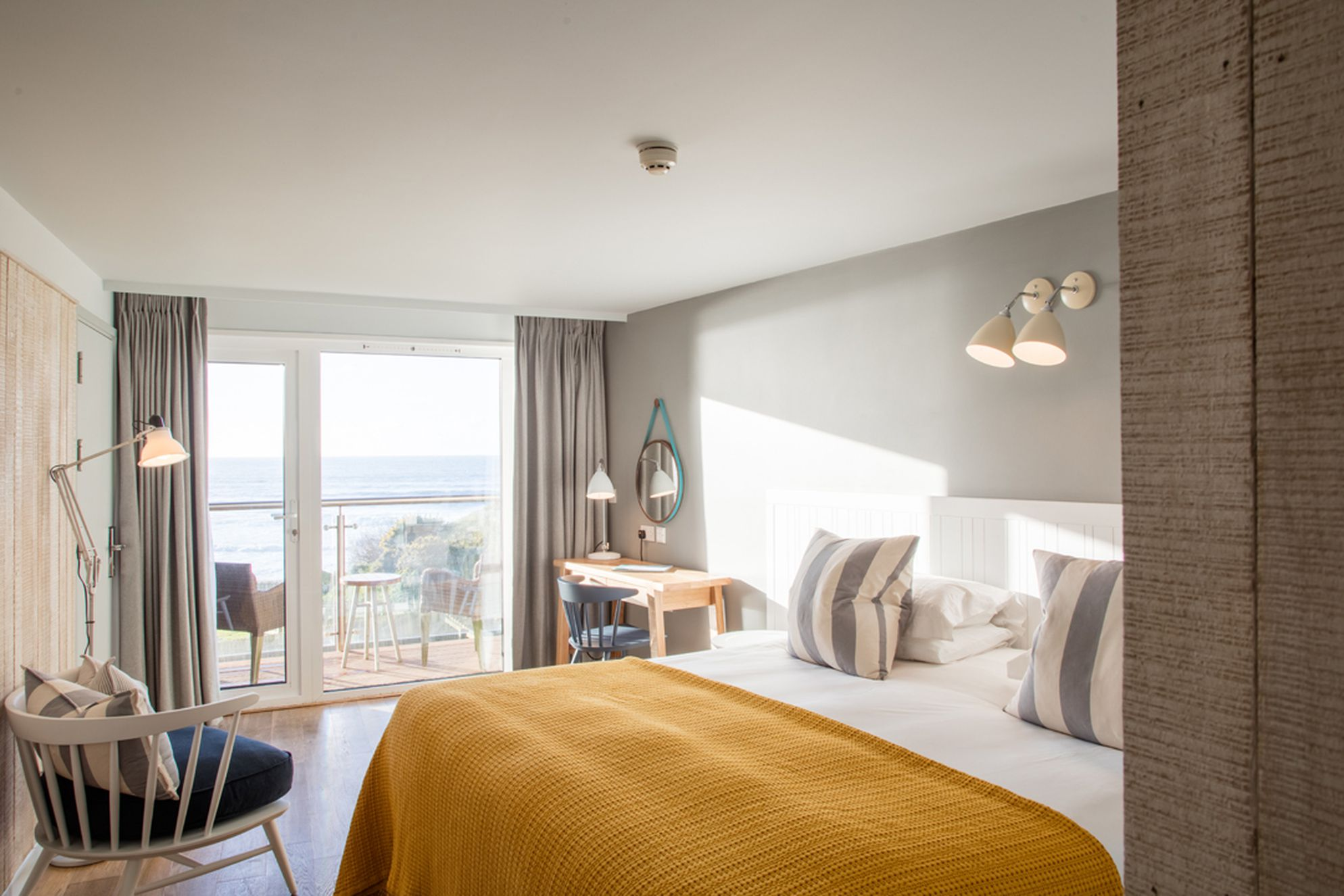 Stylish double bedroom with doors out to a balcony with seating and sea views