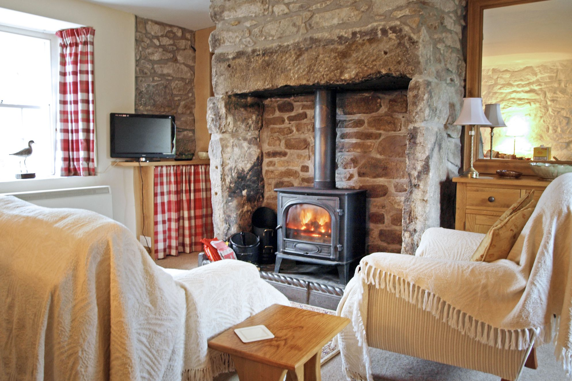 Cosy sitting room with log burner at Stennack Cottage in Cornwall