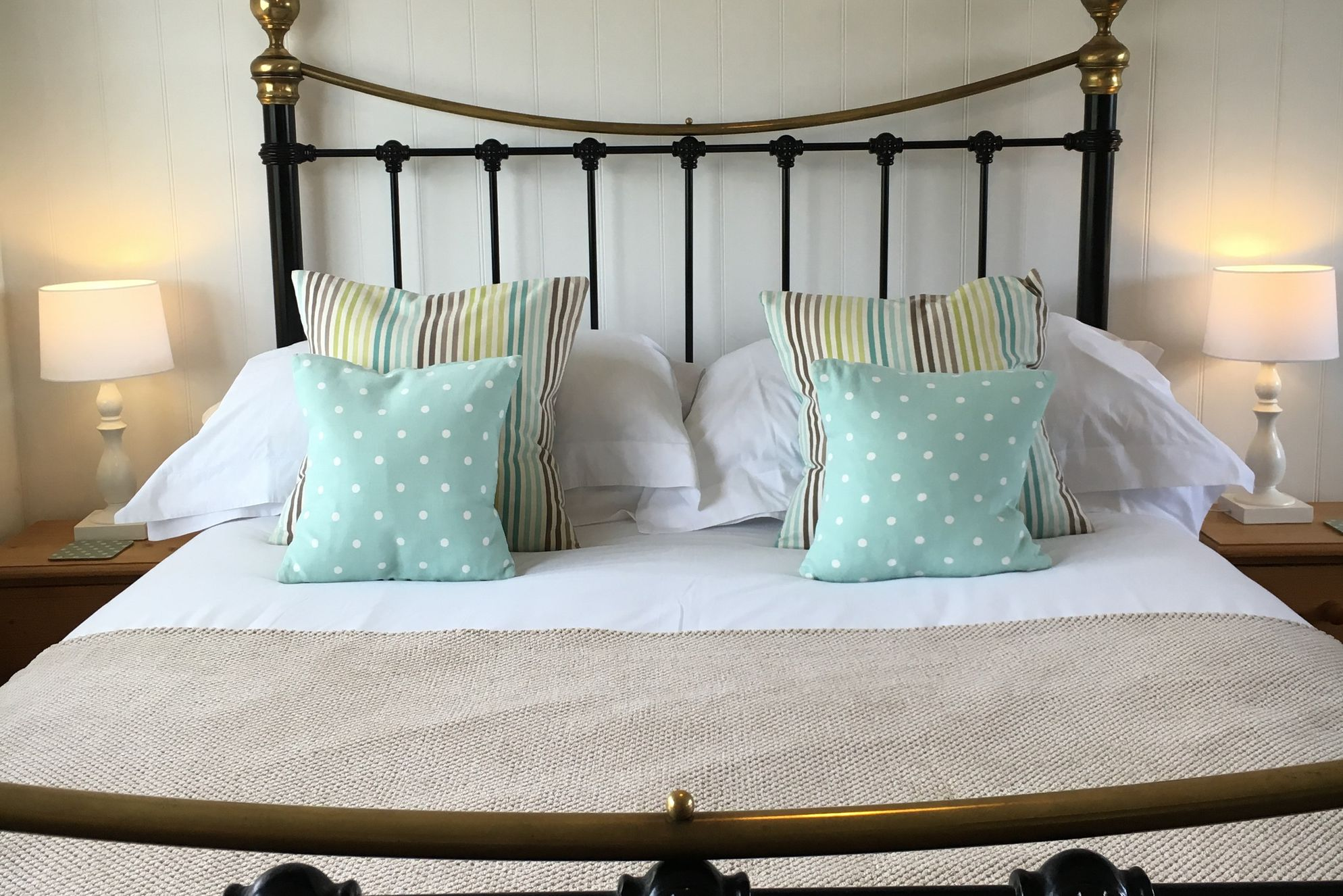 Cosy double bedroom with traditional wrought iron bed and colourful cushions