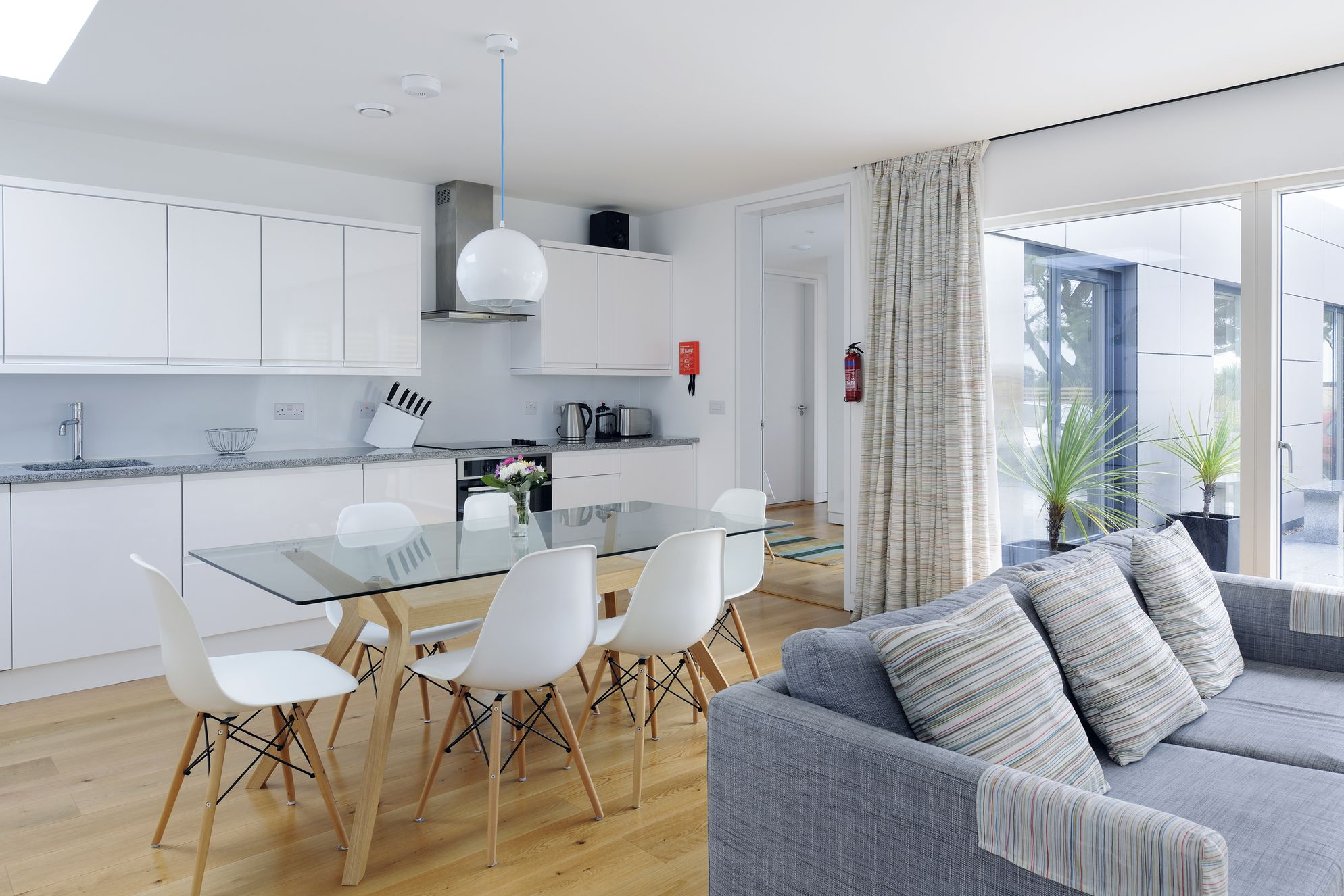 Modern, spacious and light-filled open plan kitchen with glass table and white chairs