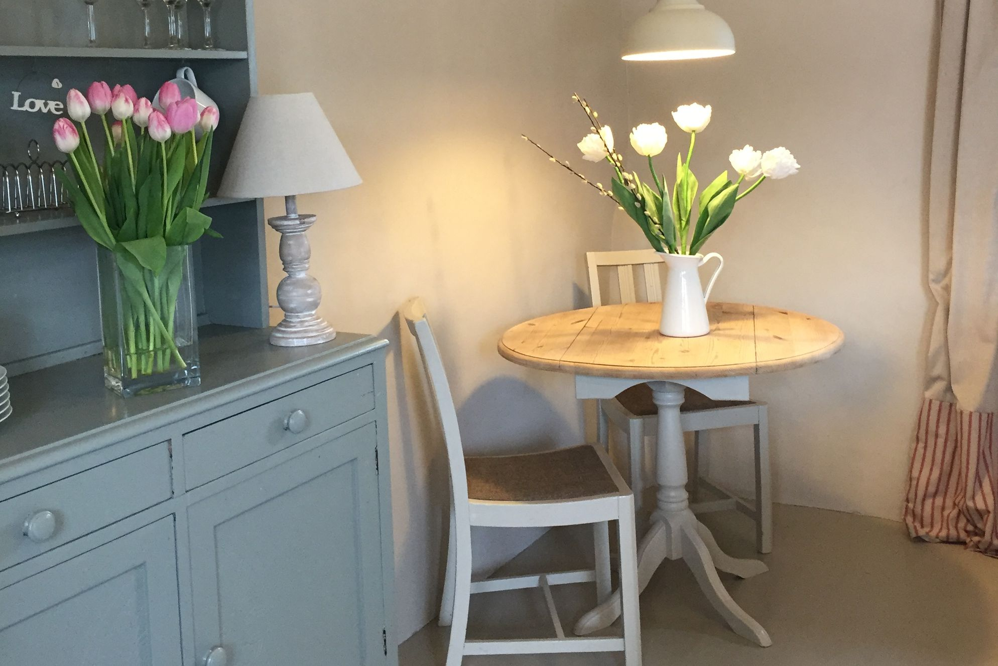 Country cottage style dining area with table for two and tulips in a vase