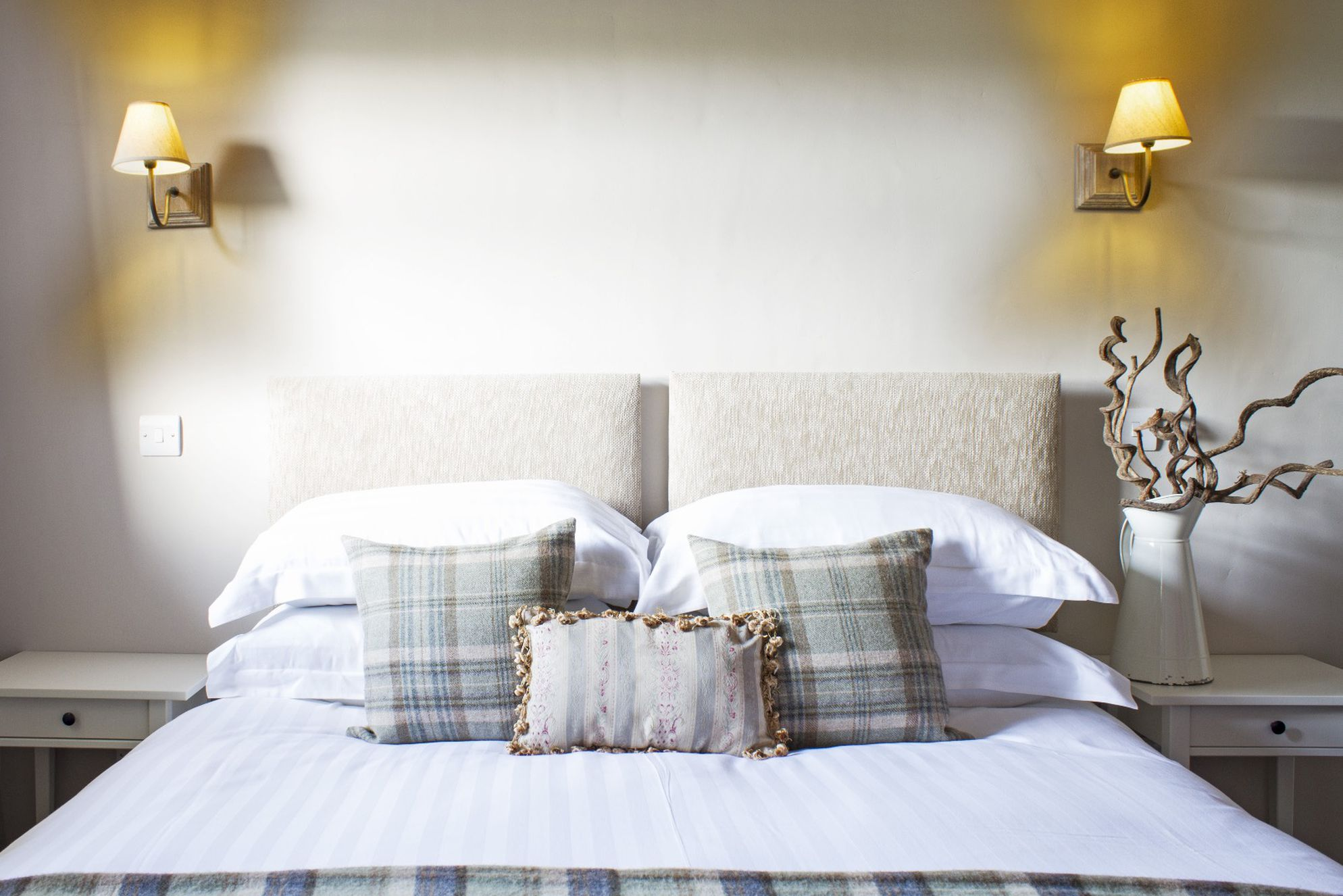 Light and airy bedroom with white linen and tartan pillows