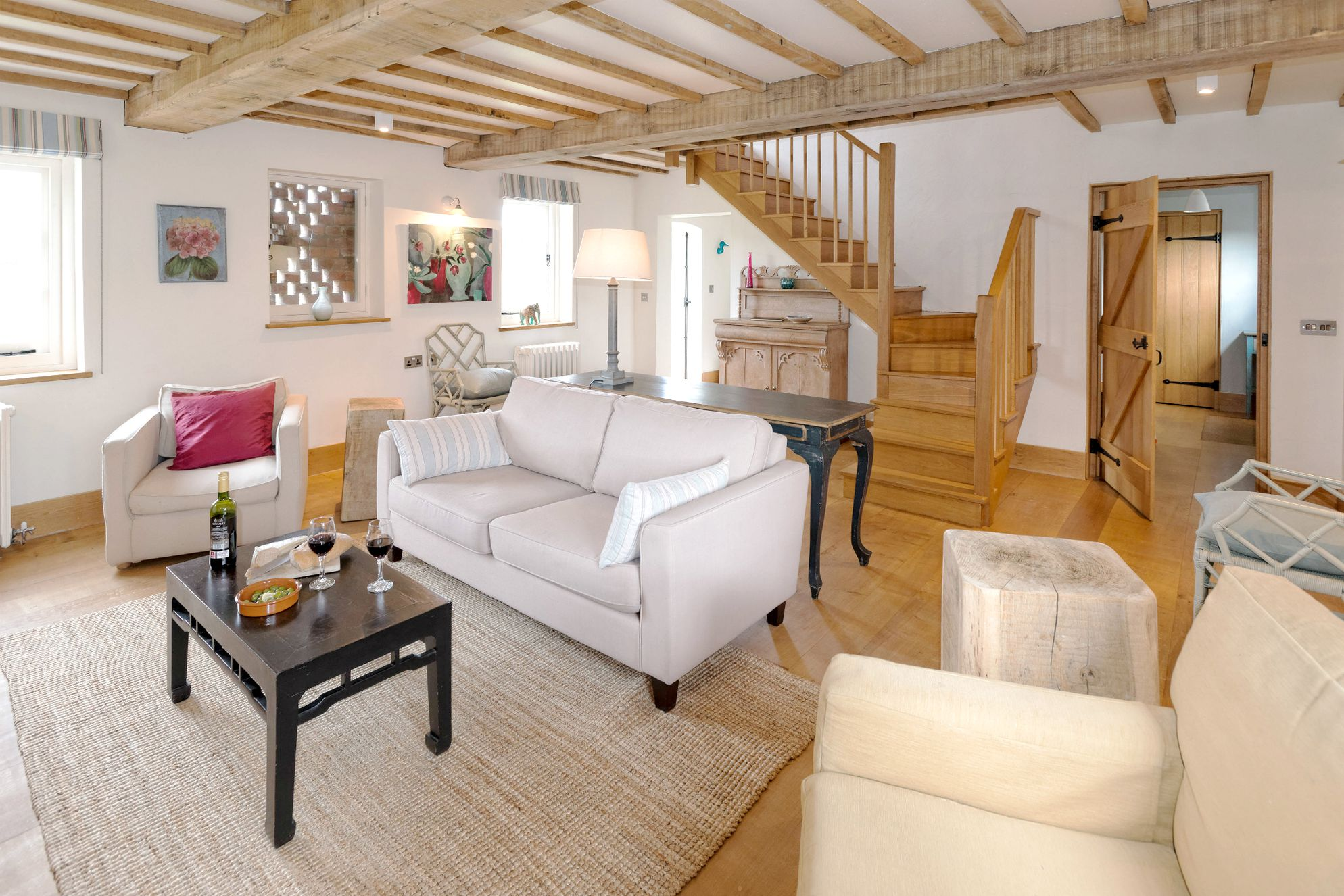 Light and spacious living area with exposed beams and neutral furniture at Field House, Collfryn Farm in Powys, Wales