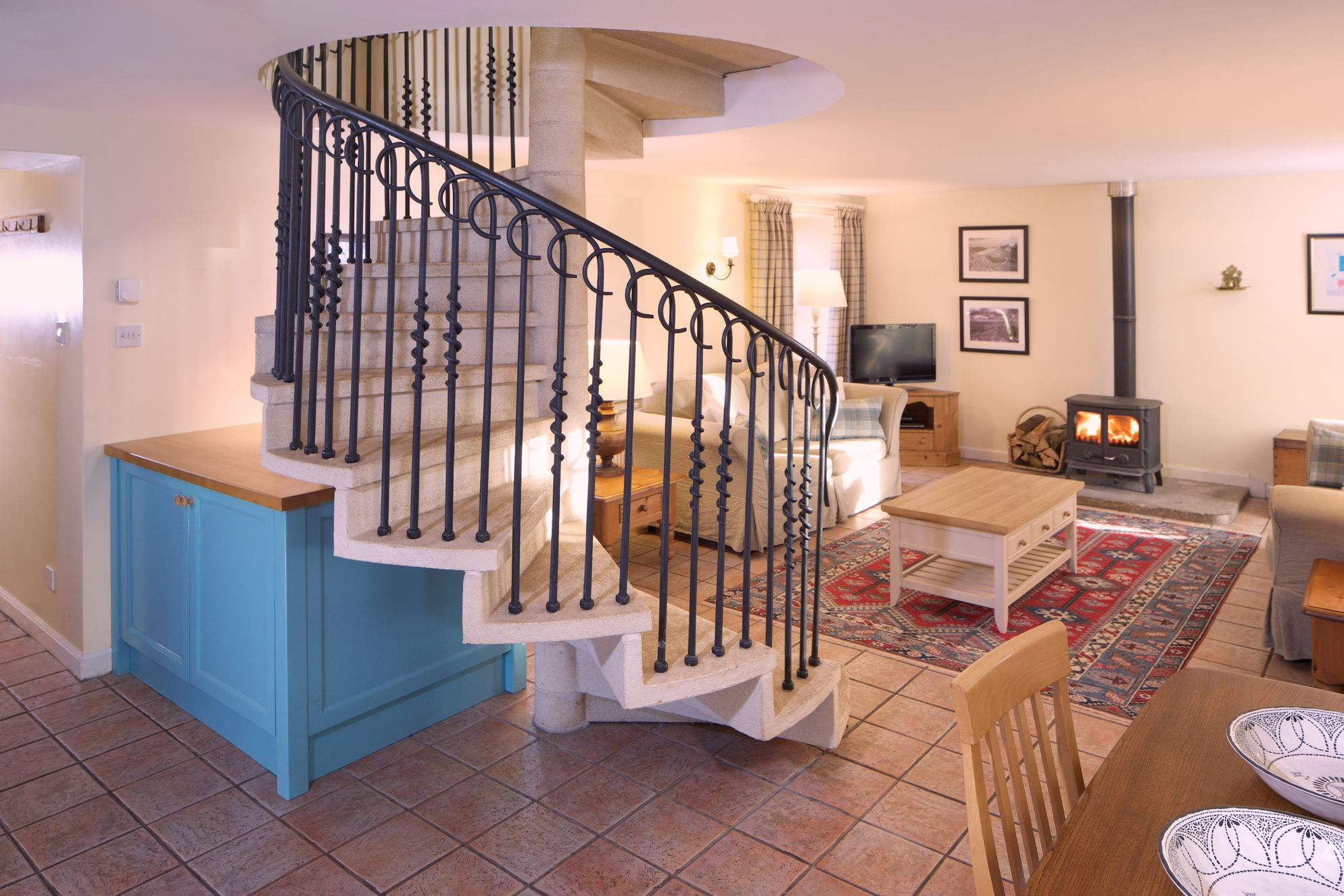 Spacious open plan kitchen, dining and living area with iron spiral staircase leading upstairs and wood burner by the sofas