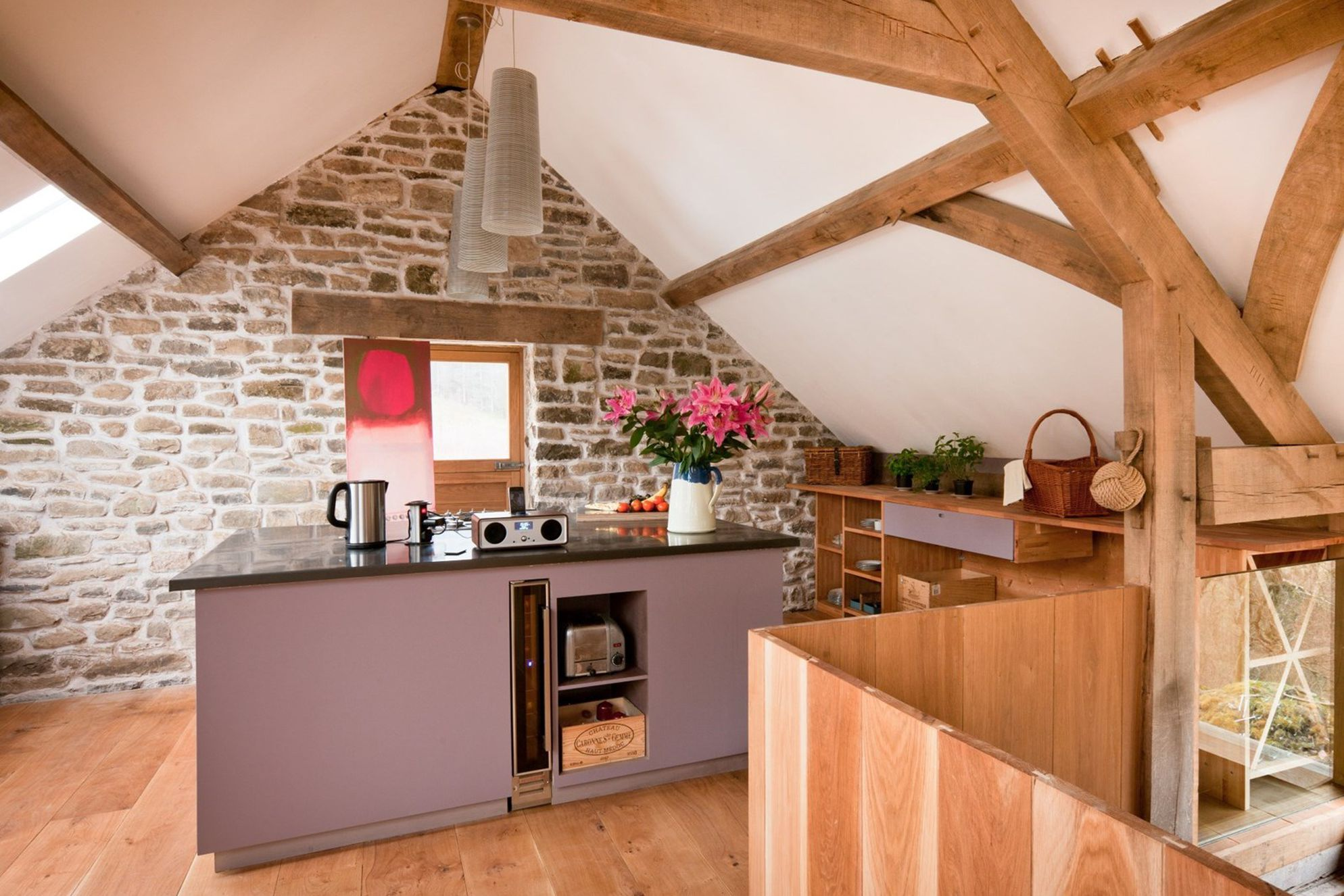 Spacious kitchen area at Red Kite Barn in Powys, Wales with nifty storage, wine cooler, coffee machine and music player