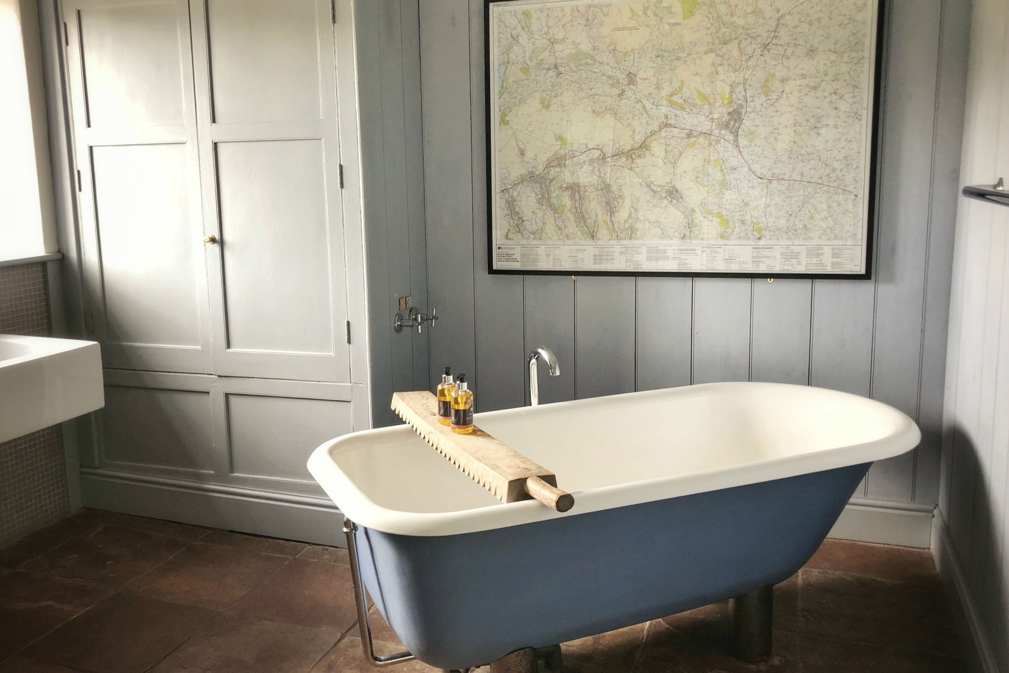 Bathroom at Sycamore House with lovely blue roll top bath against soft grey walls snd OS-style map of local area on the wall