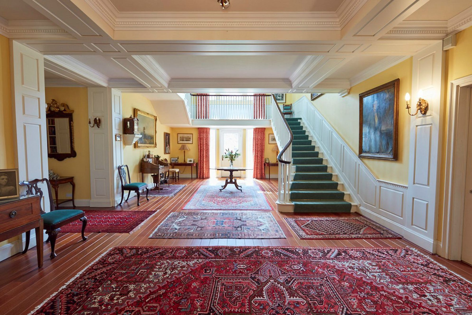 View of large, grand entrance hall at Swinburne Castle in Hexham, Northumberland with lots of tapestry rugs and stairs leading upstairs