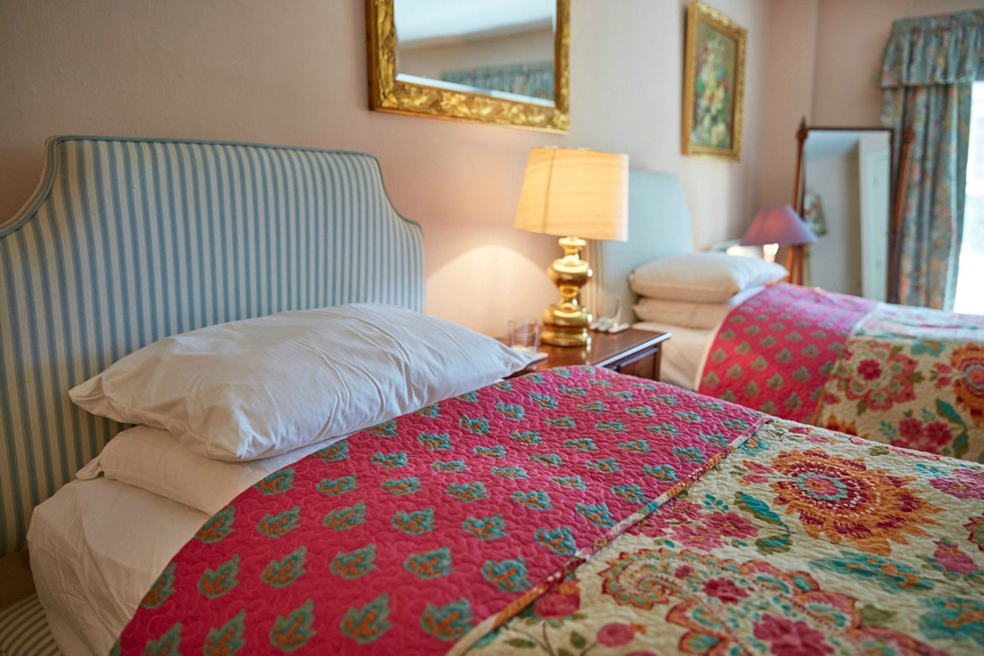 Twin bedroom with colourful and tasteful floral paisley bedding at Swinburne Castle in Hexham, Northumberland