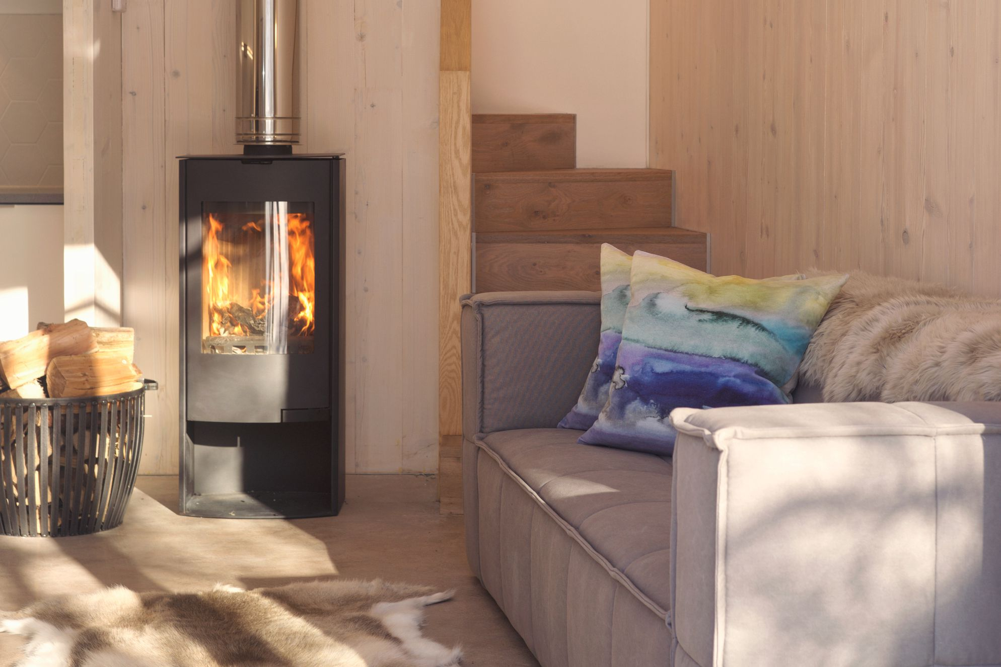 Comfy sofa in the living space at The Woodshed in Penicuik, Midlothian with real wood-burner and logs next to the fire