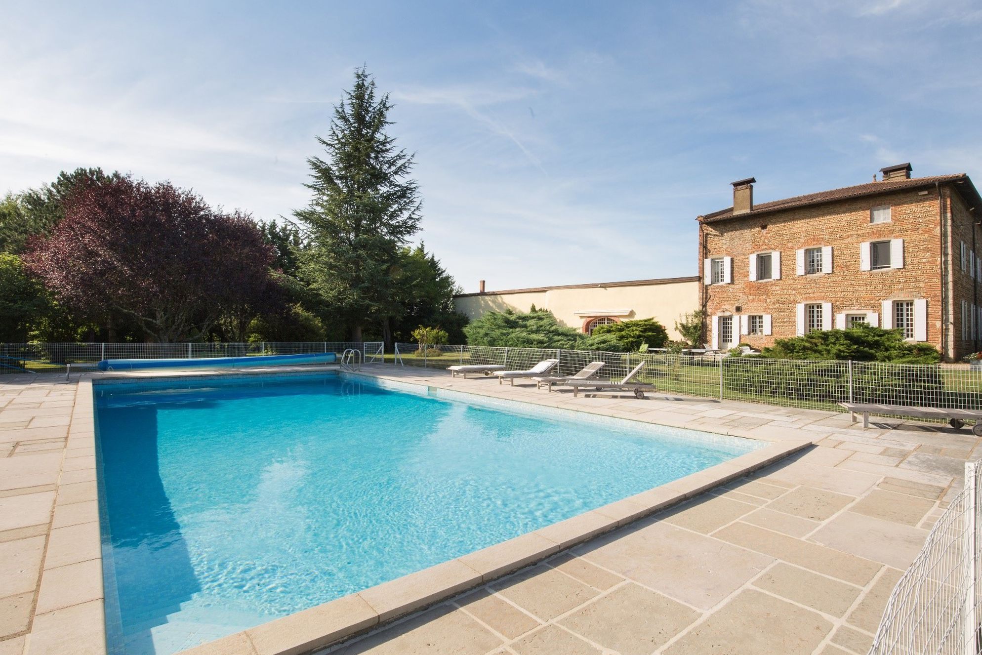 Large outdoor swimming pool in secluded setting at Domaine de Boiron