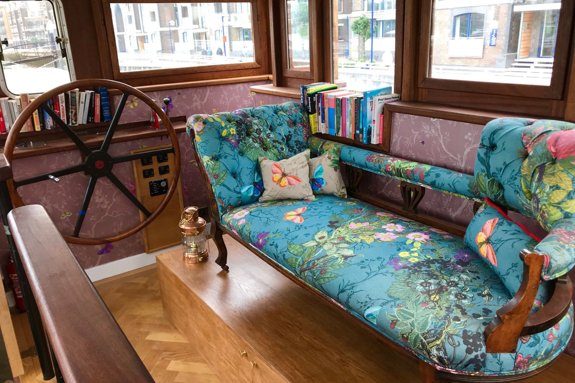 Main living area on Ara barge in Battersea, London at front of the boat with steering wheel feature and colourful floral sofa