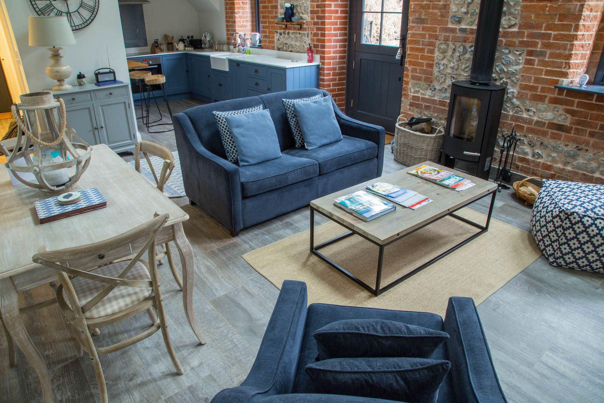Open plan kitchen and dining area at The Stable with exposed brickwork, real wood burner and luxurious blue velvet sofas