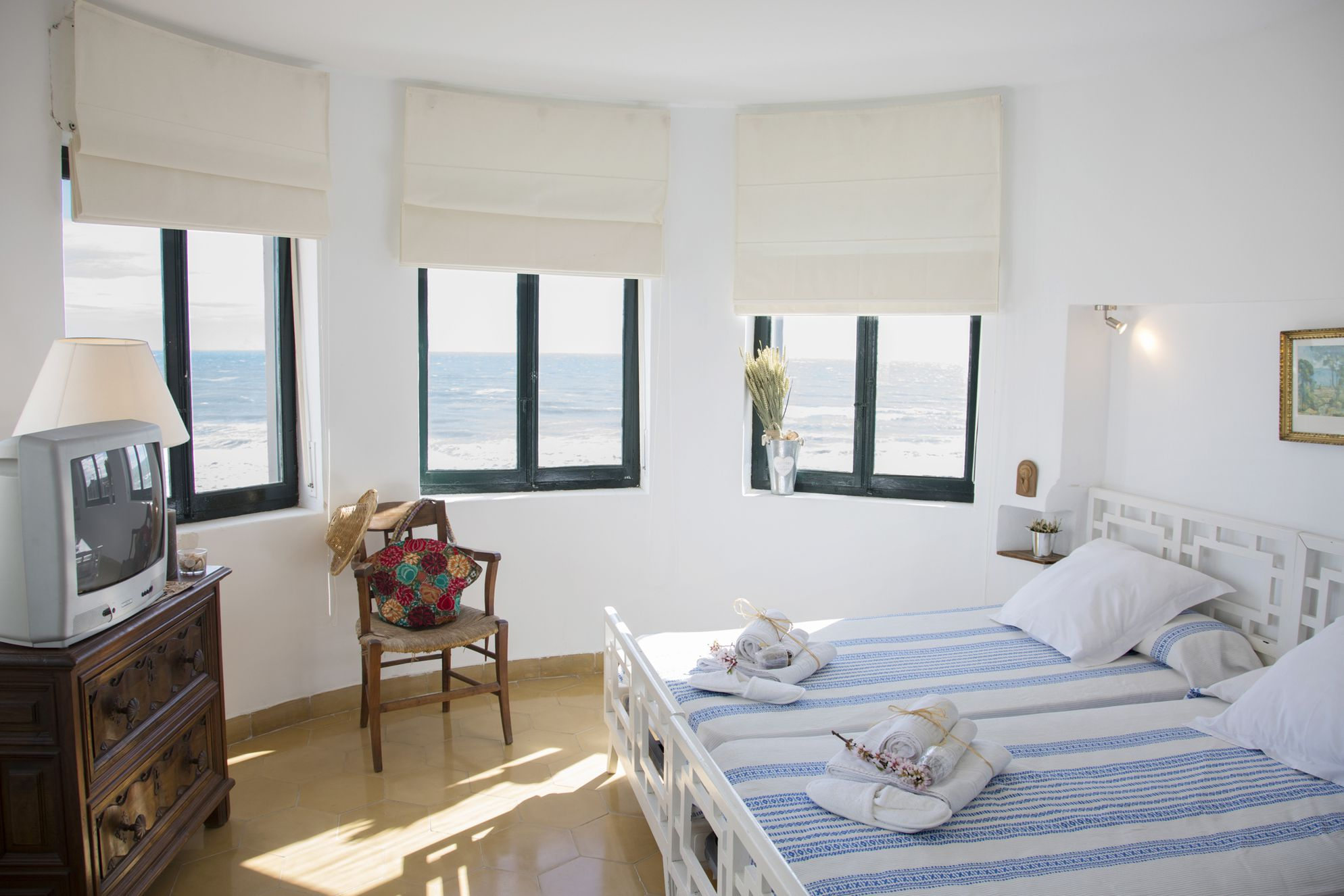Bedroom inside of Villa Socarrat with windows that look out on the sea of Valencia