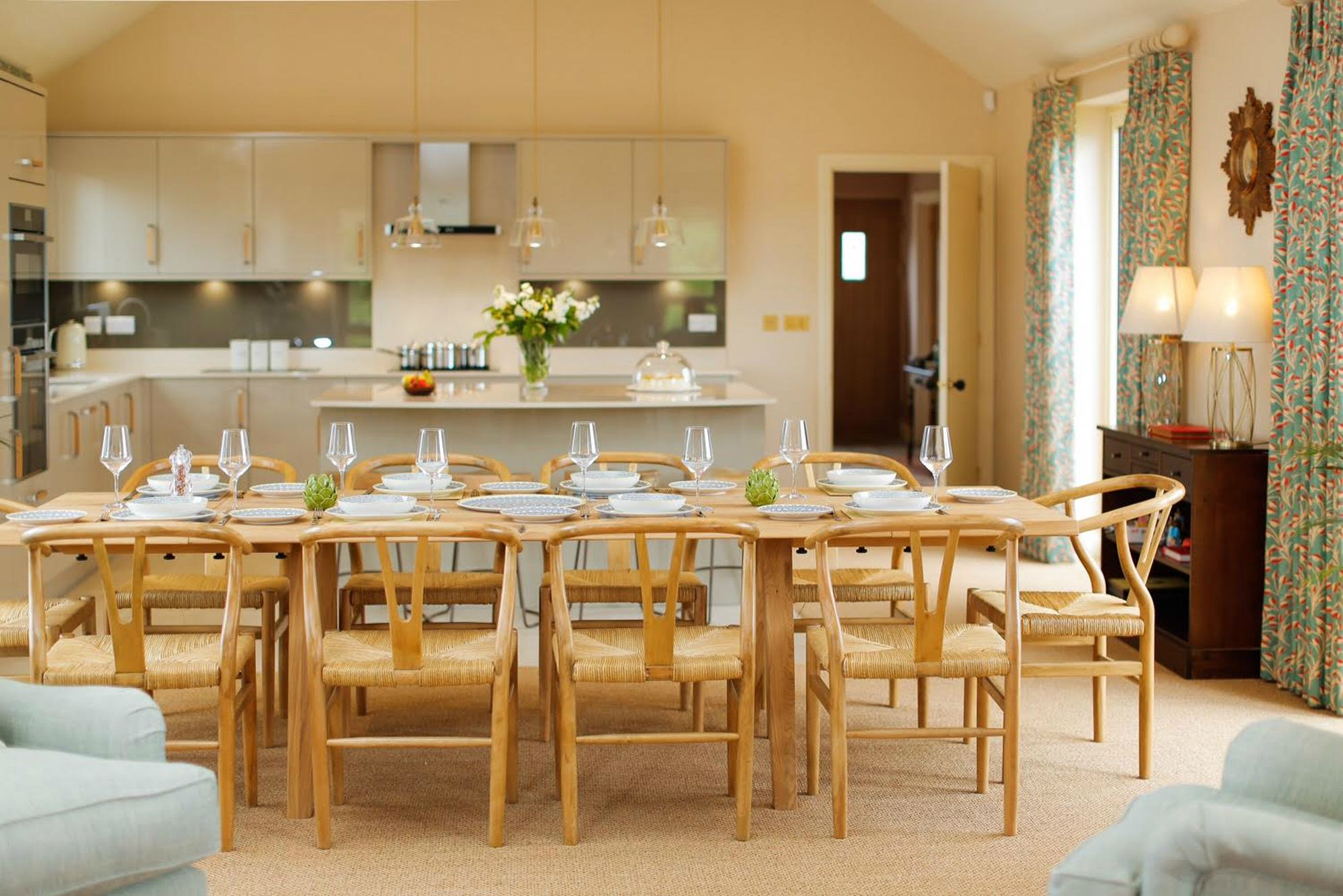 Huge dining table in Teal House Learchild with open plan kitchen behind